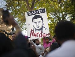 Protesters hold up a painting of a wanted poster for George Zimmerman, the neighborhood watch captain who shot and killed unarmed 17-year-old Trayvon Martin as he returned from a convenience store.