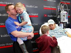 Joe Decker holds his daughter Reese, 5, while his wife, Stephanie, talks to their 8-year-old son Dominic.