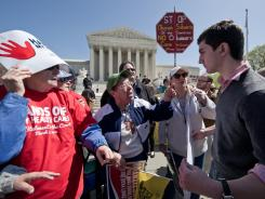 A supporter of President Obama's health care law, right, argues with several elderly women Tuesday outside the Supreme Court.
