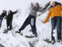 Shayla Kelly, right, Taylor Torgeson, Tanner Torgeson and Zach Lee make snow angels on March 21 after learning school was canceled. Schools across the nation are deciding what to do with an unusually high number of leftover emergency weather days.