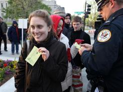 A U.S. Supreme Court Police officer hands out tickets for the final day of oral arguments on the 2010 health care law.