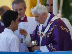 Pope Benedict XVI administers Communion during his Mass at the Plaza of the Revolution on Wednesday in Havana.