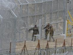 Israeli soldiers stand at the border Thursday between Majdal Shams in the Golan Heights and Syria.