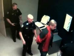 In this image from the video, George Zimmerman, right, is escorted into the Sanford, Fla., police station on Feb. 26, the night he shot and killed Trayvon Martin.