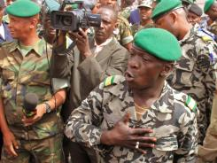 Coup leader Capt. Amadou Haya Sanogo, right, speaks during Thursday's walkabout at the airport in Bamako, Mali.