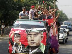 Supporters wave from a car decorated with a banner bearing portraits of Aung San Suu Kyi and her father, General Aung San, on Friday in Rangoon, Burma.