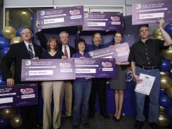 Mega Millions lottery winners pose with $319 million checks during a news conference in Schenectady, N.Y., on March 31, 2011. Lottery winners are often deluged with offers from financial planners, scam artists, friends and family.