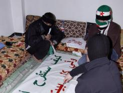 Anti-Syrian regime activists cover their faces with scarves as they prepare an Arabic banner.