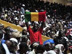 A man hold a flag of Mali as he attends a Saturday prayer ceremony in Bamako.