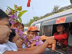 Burma opposition leader Aung San Suu Kyi greets supporters on Sunday.