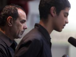 Kassim Alhimidi, left, stands by his son, Mohammed Alhimidi, during a memorial for his wife, Shaima Alawadi, at a mosque in Lakeside, Calif.