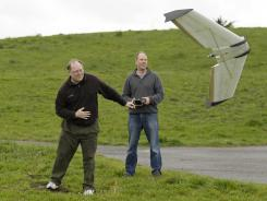 Mark Harrison, left, and Andreas Oesterer, right, watch as a Ritewing Zephyr II drone lifts off at a waterfront park in Berkeley, Calif., on Wednesday.