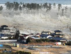 In this March 2011 file photo, waves of a tsunami hit residences after a powerful earthquake in Japan's Miyagi prefecture.