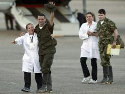 Former hostages Luis Alfonso Beltran, right, and Jorge Trujillo Solarte, second from left, arrive to an airport after being released by the Revolutionary Armed Forces of Colombia, or FARC, in Villavicencio Colombia, on Monday.