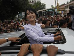 Burma's pro-democracy leader Aung San Suu Kyi greets supporters after a visit to the headquarters of her National League for Democracy Party on Monday.