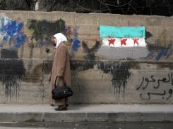 A Syrian woman and her daughter walk past a wall with a painting of the Syrian revolutionary flag in Damscus on Monday.