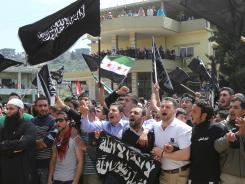 Lebanese and Syrian demonstrators chant slogans in the border area of Wadi Khaled on Sunday.