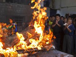 Tibetan exiles pray next to the burning funeral pyre of 27-year-old Jamphel Yeshi, who passed away after he immolated himself.