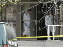 Police investigators work at the entrance of Oikos University in Oakland on Tuesday.