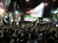 Syrians wave revolutionary flags and chant slogans at a Monday night protest against President Bashar Assad in a neighborhood of Damascus.
