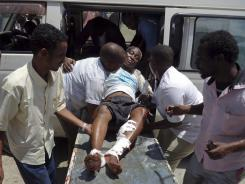 Medical personnel help a man wounded in a blast at the Somali National Theater in Mogadishu.