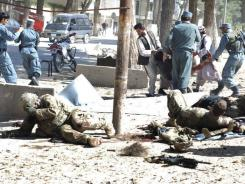 Wounded U.S. soldiers lie on the ground at the scene of a suicide attack in Maimanah, Afghanistan on Wednesday.
