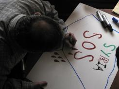 Syrian activists prepare signs for upcoming protests at a house in a neighborhood in Damascus, Syria.