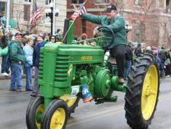Sen. Jon Tester, D-Mont., rides a John Deere tractor in the annual St. Patrick's Day parade in Butte, Mont., on March 17.