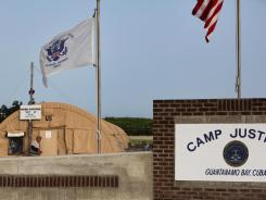 Flags hang above the sign marking the Camp Justice compound at Guantanamo Bay, Cuba.