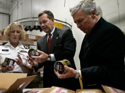 U.S. Health and Human Services Sec. Michael Leavitt (C) and Food and Drug Administration (FDA) Commissioner Andrew von Eschenbach (R) listen as FDA consumer safety officer Teresa Fox demonstrates inspection technique on imported crab meat during a tour.
