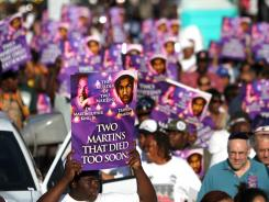 Hundreds march holding posters in Miami's Liberty City neighborhood during a rally on April 4 in Miami.