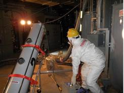 A worker operates an endoscope to take photos of water in the Unit 2 reactor's primary containment vessel at the Fukushima Dai-ichi nuclear power plant.