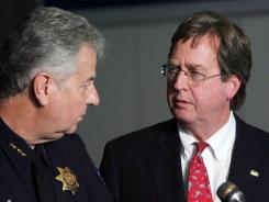 Tulsa Mayor Dewey Bartlett, right, chats with Tulsa Chief of Police Chuck Jordan during a news conference at the Tulsa Police Department, on Saturday.