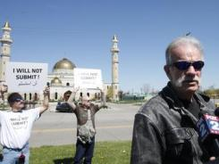 Quran-burning Pastor Terry Jones speaks with members of the media while protesting against Islam on Saturday.