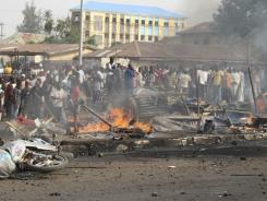 People gather at the site of a bomb explosion on a road in Kaduna, Nigeria, on Sunday.