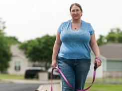 Dana Kendall, a 29-year-old Navy wife, takes her pit bull Toni for a walk around their neighborhood in San Antonio.