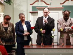 From left, Renae Shoates, Margaret Love, Rev. Marlin Lavanhar of All Souls Unitarian Church and Dr. Warren Blakney participate in a remembrance of the shooting victims in Tulsa, Okla.