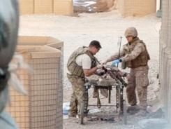 Army Staff Sgt. Ben Summerfield, left, removes an unexploded ordnance from Marine Cpl. Winder Perez, while Lt. Cmdr. James Gennari treats Perez on Jan. 12 in Afghanistan.