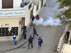 Tunisian demonstrators run for cover as police fire tear gas to break up a protest in Tunis.