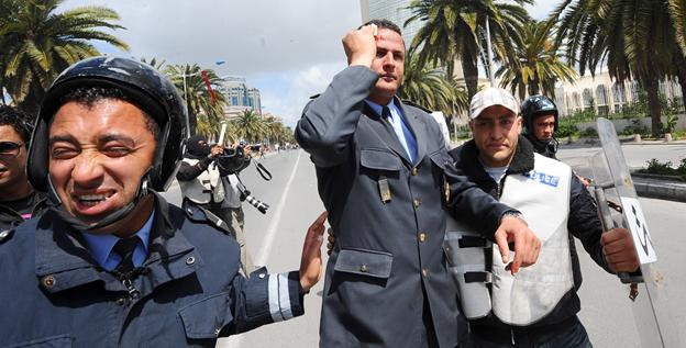 Tunisian police walk with an officer injured during a clashes between Tunisian protesters and security forces on Monday in Tunis.