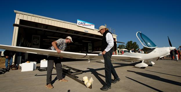 Team members reattach the wings to their PhoEnix aircraft after pulling it out the weigh-in hanger during the 2011 Green Flight Challenge competition.