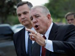 Craig Sonner, left, and Hal Uhrig, right, speak with the media Tuesday about having lost contact with their client, George Zimmerman.