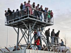 Syrians, who fled the uprising in their country, watch the border Monday from a refugee camp in Kilis, Turkey.
