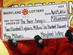 The three anonymous winners of the Maryland portion of the record Mega Millions jackpot pose for a photo in Baltimore on April 9.
