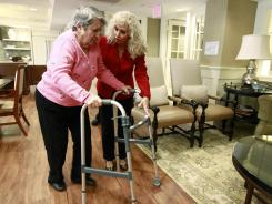 Alexis McKenzie, executive director of The Methodist Home of the District of Columbia Forest Side, an Alzheimer's assisted-living facility, walks with resident Catherine Peake. Dementia can sneak up on families because its sufferers are pretty adept at covering lapses early on, longer if their spouses are there to compensate.