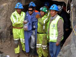 Miner Javier Tapia, second from left, is helped out of the Cabeza de Negro mine in Yauca del Rosario, Peru, on Wednesday.