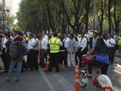People begin returning to a building that was evacuated after an earthquake was felt in Mexico City.