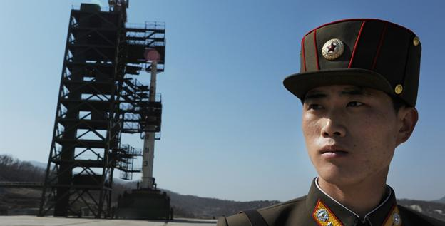 A North Korean soldier stands guard in front of an Unha-3 rocket at Tangachai-ri space center on Sunday.
