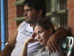 Analia Bouter and her husband, Fabian Veron, sit outside the hospital in Resistencia, Argentina, on Wednesday.