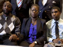 The mother of Trayvon Martin, Sybrina Fulton, center, closes her eyes as she watches a news conference with special prosecutor Angela Corey announcing charges against George Zimmerman.